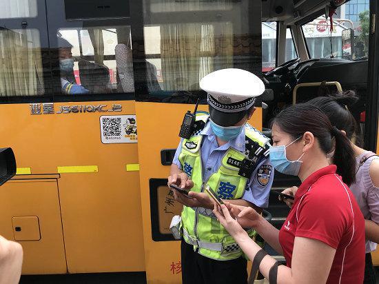 交警教家长通过手机扫描二维码。信息时报记者 胡瀛斌 摄