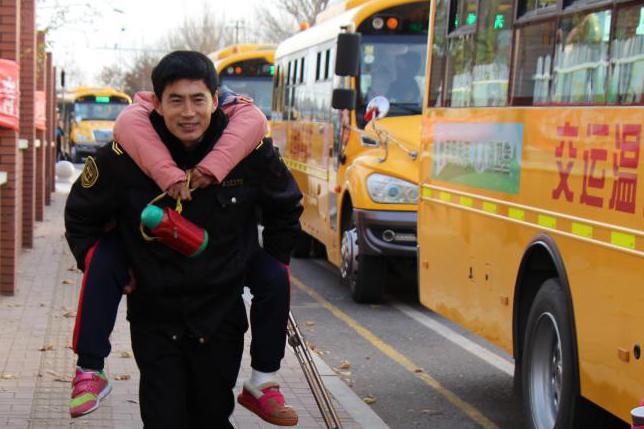 校车驾驶员寒冬背学生上学 定格在冷风中的温暖瞬间